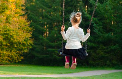 Ett barn sett bakifrån som gungar på en gunga.