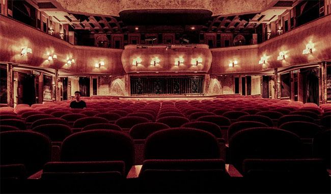 Person sitter ensam i en teatersalong