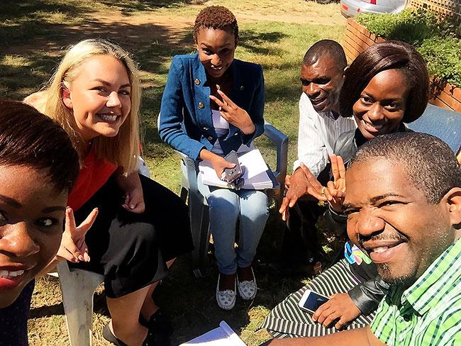 Sex personer sitter och ler