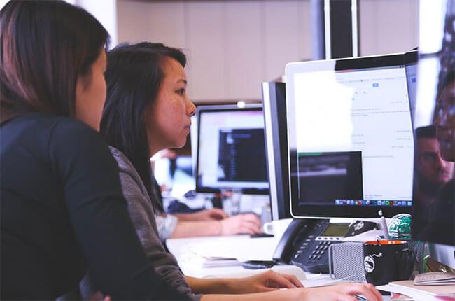 Två personer sitter framför en dator.
